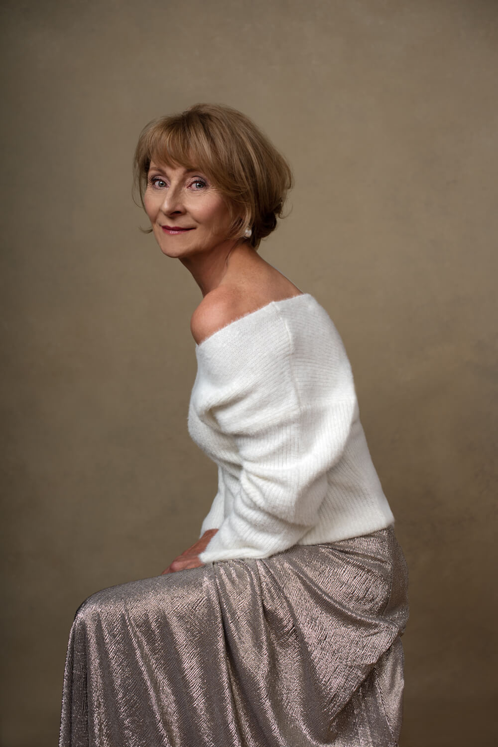 wise woman in a white jumper and silver skirt