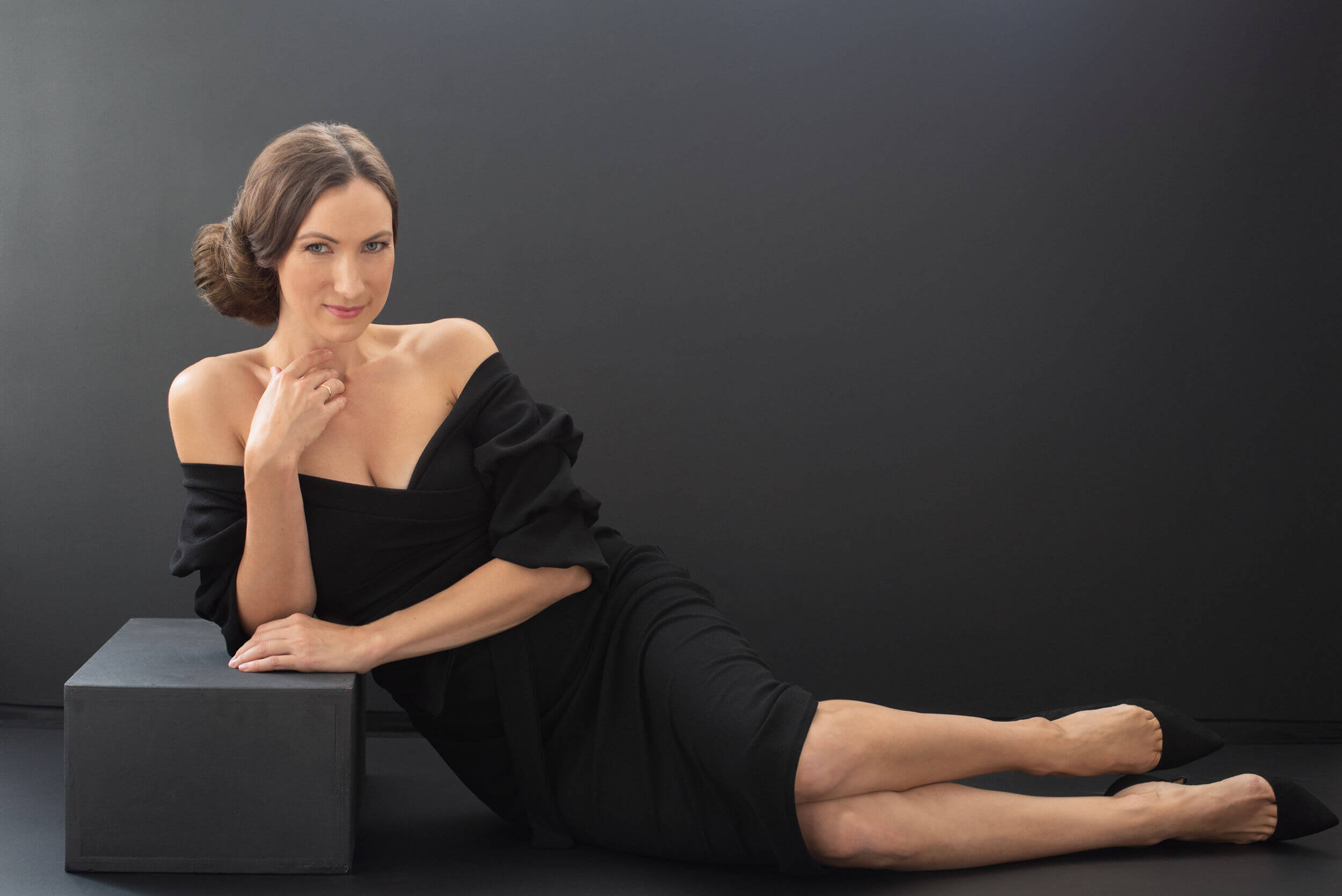 sexy woman in a black dress laying in the floor