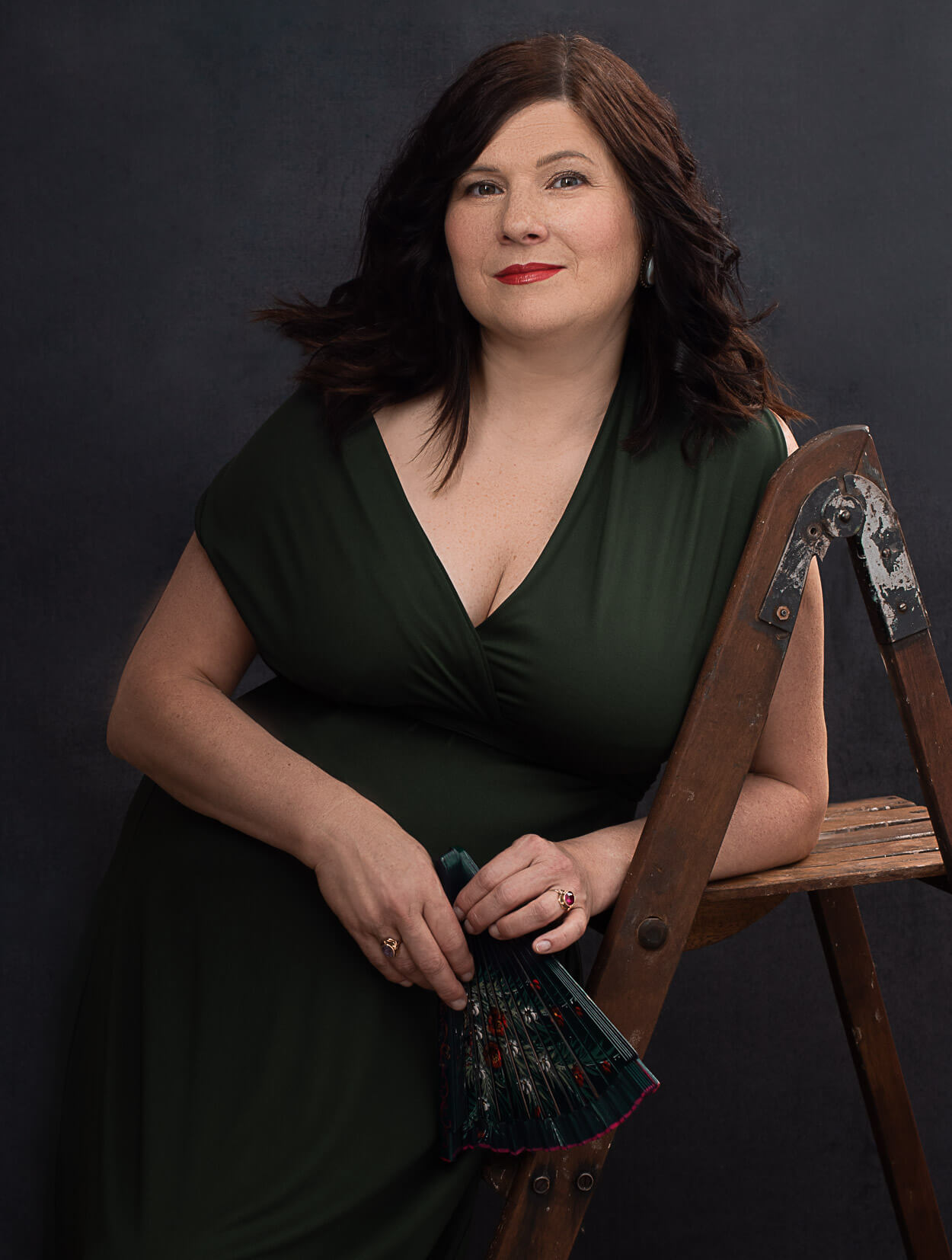 a curvy woman in a green dress leaning against the ladder